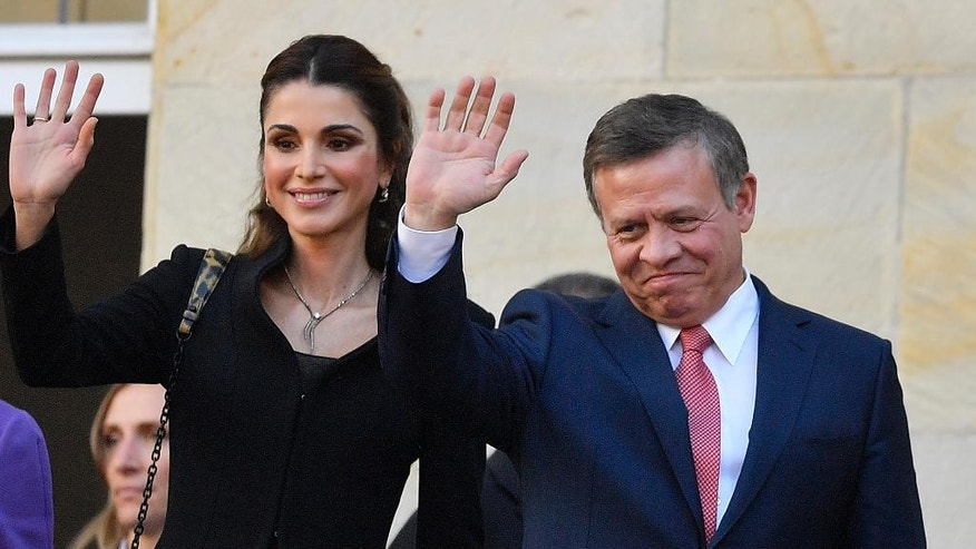 King Abdullah of Jordan and Queen Rania wave to citizens on the historic town hall balcony in Muenster, Germany, Saturday, Oct. 8, 2016. King Abdullah was awarded the Peace Prize of Westphalia in recognition of his endeavors for peace and international security and stability. (AP Photo/Martin Meissner)