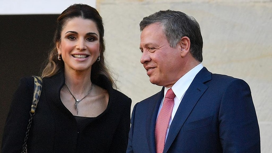 King Abdullah of Jordan and Queen Rania are celebrated by citizens on the historic town hall balcony in Muenster, Germany, Saturday, Oct. 8, 2016. King Abdullah was awarded the Peace Prize of Westphalia in recognition of his endeavors for peace and international security and stability. (AP Photo/Martin Meissner)