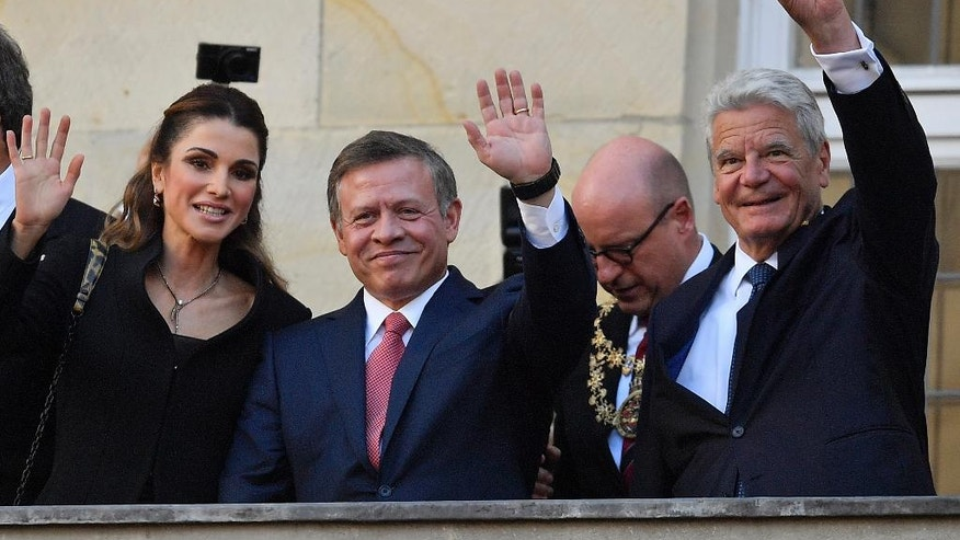 Queen Rania and King Abdullah of Jordan and German president Joachim Gauck, from left, wave to citizens on the historic town hall balcony in Muenster, Germany, Saturday, Oct. 8, 2016. King Abdullah was awarded the Peace Prize of Westphalia in recognition of his endeavors for peace and international security and stability. (AP Photo/Martin Meissner)