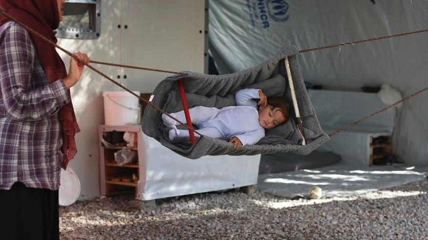 A woman uses a makeshift swing for a small child at the  Kara Tepe camp for refugees and other migrants on Lesbos island, Greece, on Thursday, Oct. 6, 2016. More than a million migrants and refugees crossed through Greece and on to other EU countries since the start of 2016, while over 60,000 have been stranded in the country since the EU-Turkey deal took effect and the Balkan transit route north was closed. (AP Photo/Petros Giannakouris)