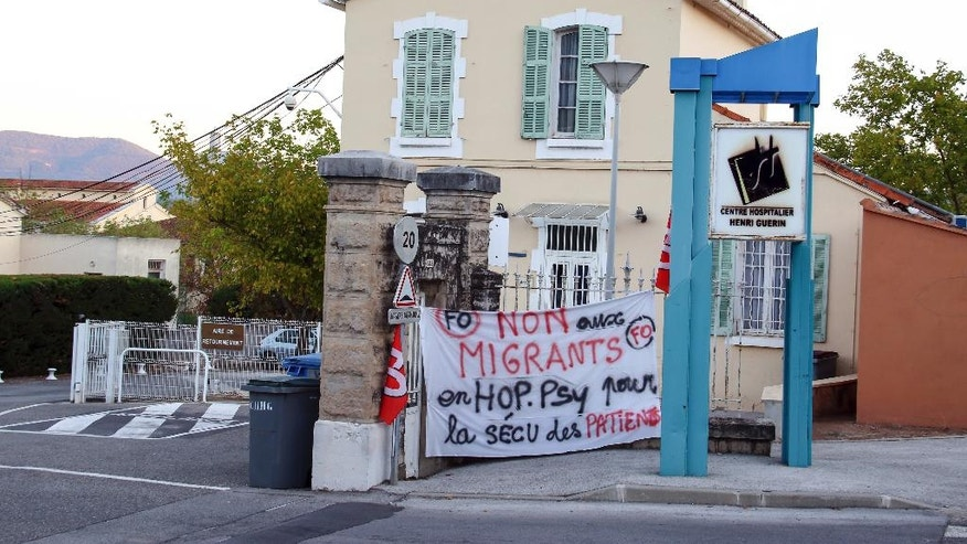 "A banner reads : "" No to migrants at psychiatric hospital for the security of patients"", as the government plans to house migrants in an abandoned wing of a psychiatric hospital, in Pierrefeu, southeastern France, Saturday, Oct. 8, 2016. French villagers are protesting the arrival of migrants who are being spread out around the country as the government shuts down the slum-like camp in Calais that has become a flashpoint in Europe's migrant crisis. (AP Photo/Philippe Farjon)"