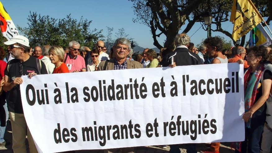 "Left-wing activists hold a banner reading : "" Yes to solidarity and welcome to migrants and refugees "" during a demonstration to welcome the migrants, in Pierrefeu, southeastern France, Saturday, Oct. 8, 2016. French villagers are protesting the arrival of migrants who are being spread out around the country as the government shuts down the slum-like camp in Calais that has become a flashpoint in Europe's migrant crisis. (AP Photo/Philippe Farjon)"