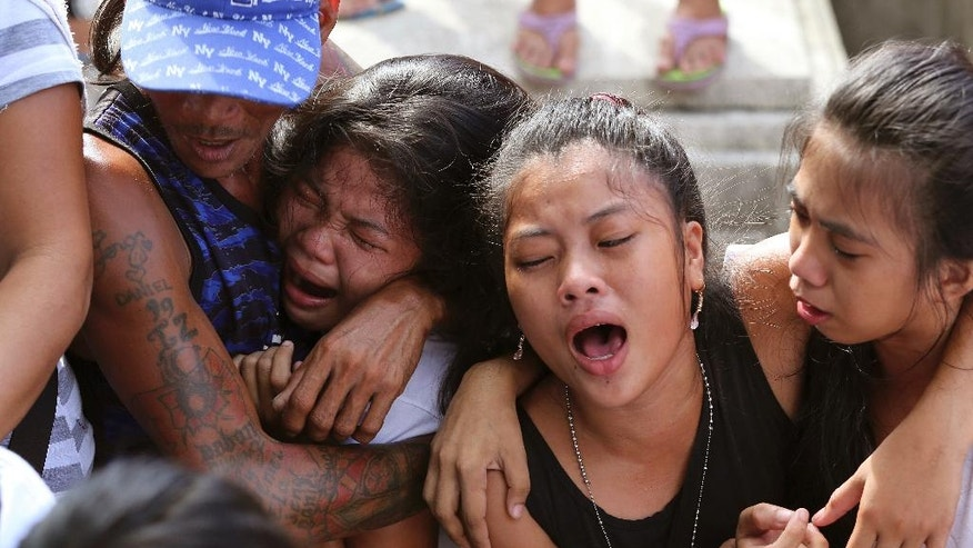 "In this Friday Sept. 12, 2016 photo, relatives and friends grieve at the funeral of an alleged drug suspect Robert Manuel Jr. at the Manila's North Cemetery, Philippines after Manuel was killed with two others during a buy-bust police operation as part of the continuing ""War on Drugs"" campaign of Philippine President Rodrigo Duterte. In just 100 days in office, Duterte has stirred a hornet's nest by picking a fight with Barack Obama, the United Nations, the European Union and others who have criticized his brutal crackdown against drugs that has left more than 3,600 suspects dead. (AP Photo/Aaron Favila)"