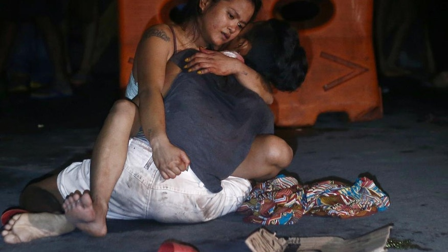In this July 23, 2016 photo, Jennilyn Olayres cuddles her live-in partner alleged drug user and pusher Michael Siaron, after he was killed by unknown assailants at an intersection in Pasay city south of Manila, Philippines. In just 100 days in office, Philippine President Rodrigo Duterte has stirred a hornet's nest by picking a fight with Barack Obama, the United Nations, the European Union and others who have criticized his brutal crackdown against drugs that has left more than 3,600 suspects dead. (AP Photo/Linus G. Escandor II)