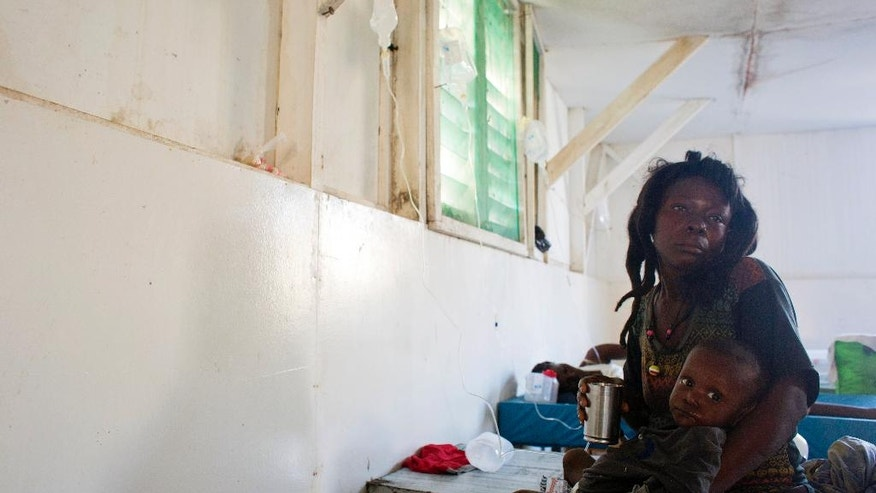 A woman holds her boy who's suffering cholera in the state hospital after Hurricane Matthew, in Jeremie, Haiti. Saturday Oct. 8, 2016.   Aid has begun pouring into the hard-hit town,  where thousands of homes were damaged or destroyed and many people were running low on food and facing an increased risk for cholera.  ( AP Photo/Dieu Nalio Chery)