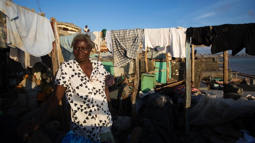 Yoleine Casimir stands in her destroyed house caused by Hurricane Matthew, in Jeremie, Haiti. Saturday Oct. 8, 2016.   Aid has begun pouring into the hard-hit town,  where thousands of homes were damaged or destroyed and many people were running low on food and facing an increased risk for cholera.  (AP Photo/Dieu Nalio Chery)