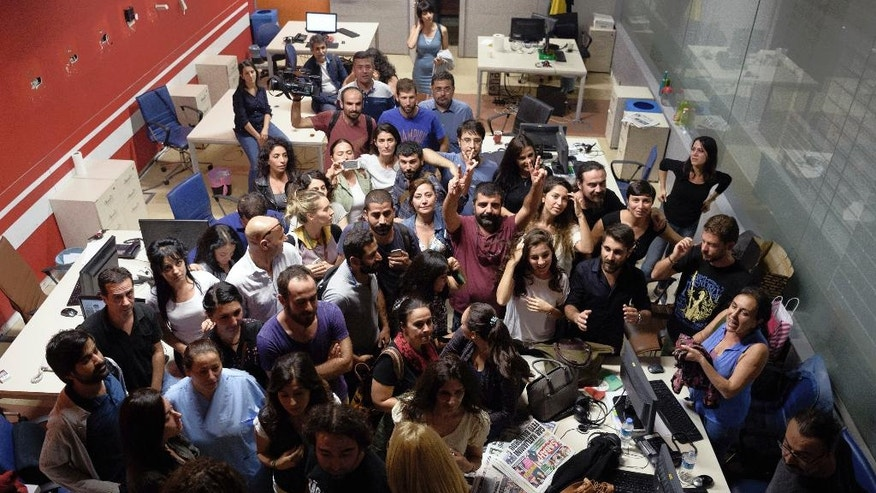 In this photo taken Tuesday, Oct. 4, 2016, the journalists of the IMC-TV gather in their Istanbul office after their television channel was shut down. A dozen police officers, joined by officials from Turkey's treasury and the county's broadcasting watchdog, marched into the headquarters of the pro-Kurdish IMC-TV television station, sealed off the control rooms and forced the channel off the air during a live program on democracy.(AP Photo)