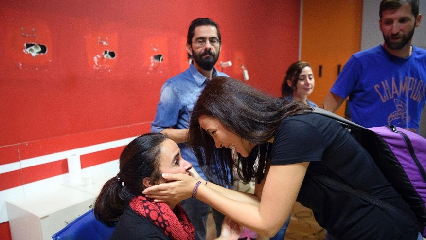 In this photo taken Tuesday, Oct. 4, 2016, the journalists of the IMC-TV react in their Istanbul office after their television channel was shut down. A dozen police officers, joined by officials from Turkey's treasury and the county's broadcasting watchdog, marched into the headquarters of the pro-Kurdish IMC-TV television station, sealed off the control rooms and forced the channel off the air during a live program on democracy.(AP Photo)