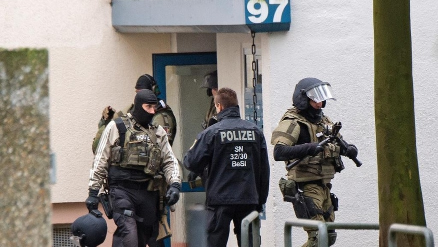 Police officers leave an apartment in the eastern city of in Chemnitz, Germany, on Saturday.