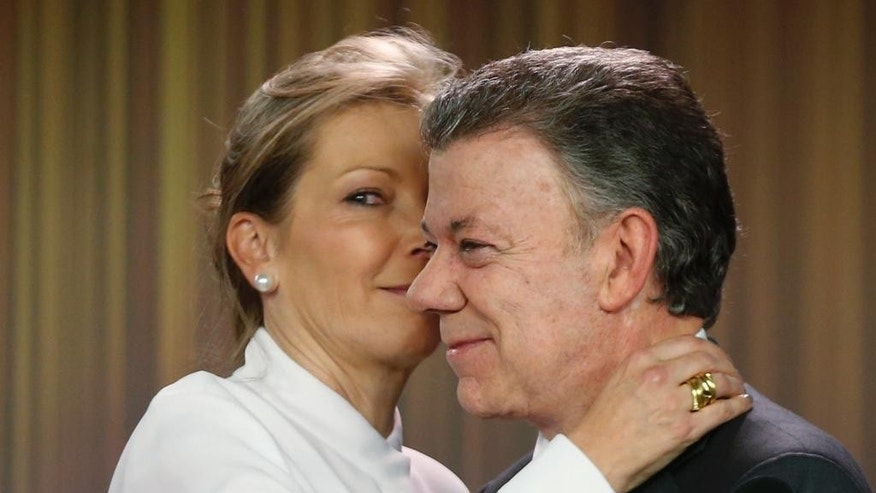 Colombia's President Juan Manuel Santos is embraced by his wife Maria Clemencia Rodriguez after speaking to journalists at the presidential palace in Bogota, Colombia, Friday, Oct. 7, 2016.  Santos won the Nobel Peace Prize Friday, just days after voters narrowly rejected a peace deal he signed with rebels of the Revolutionary Armed Forces of Colombia, FARC.  (AP Photo/Fernando Vergara)