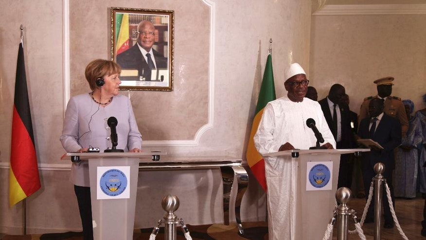 German Chancellor Angela Merkel, left, looks at Malian President Ibrahim Boubacar Keita, during a press briefing after her arrival at Bamako, Mali, Sunday, Oct. 9, 2016. German Chancellor  Merkel is on a three day tour in Africa, visiting, Mali, Niger, and Ethiopia. (AP Photo/Baba Ahmed)
