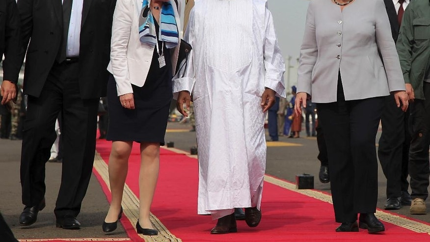 Malian President Ibrahim Boubacar Keita, third left, walk with German Chancellor Angela Merkel, right, after her arrival at the airport in Bamako, Mali, Sunday, Oct. 9, 2016. German Chancellor  Merkel is on a three day tour in Africa, visiting, Mali, Niger, and Ethiopia. (AP Photo/Baba Ahmed)