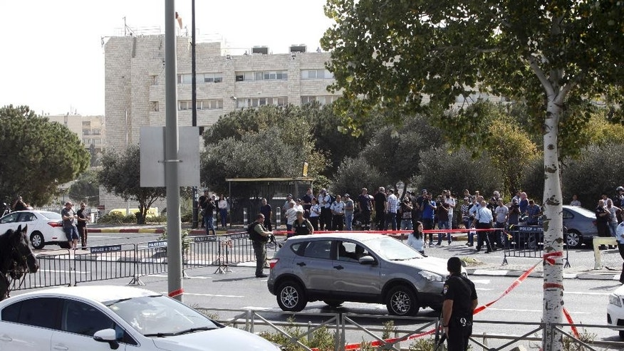 Israeli police secures the scene of a shooting attack in Jerusalem Sunday, Oct. 9, 2016. A Palestinian motorist launched a shooting spree near the Israeli police headquarters in Jerusalem Sunday, killing  two and wounding several more  before being shot dead, Israeli police and emergency services said. (AP Photo/Mahmoud Illean)