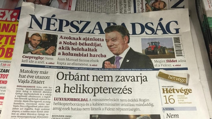 "RE-SENDING AS A ROTATED VERSION - A newsstand including Saturday papers with Nepszabadsag daily is pictured in Budapest, Saturday, Oct. 8, 2016. Headline of Nepszabadsag reads: ""Orban not bothered by helicoptering"". It refers to a scandal uncovered by Nepszabadsag about the extravagant travel habits of a top minister in the government of Prime Minister Viktor Orban. (AP Photo/Andras Nagy)"