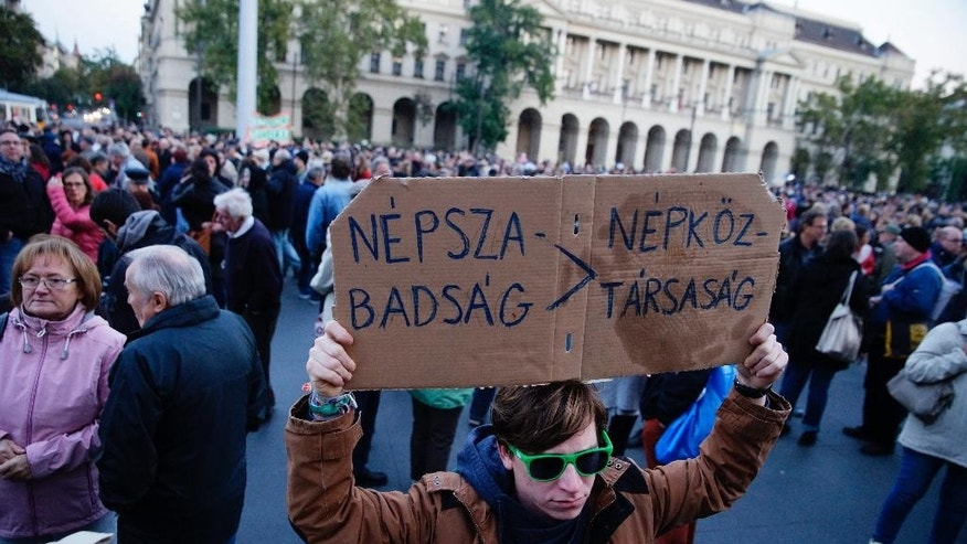"Demonstrators gather in front of  the Parliament building to show their solidarity with the Hungarian political daily Nepszabadsag in Budapest, Hungary, Saturday, Oct. 8, 2016. Earlier the day the publishing company Mediaworks suspended the publication of both the print and online editions of the paper until it comes up with a new business model. The placard reads: ""Nepszabadsag, People's Republic"". (Zoltan Balogh/MTI via AP)"