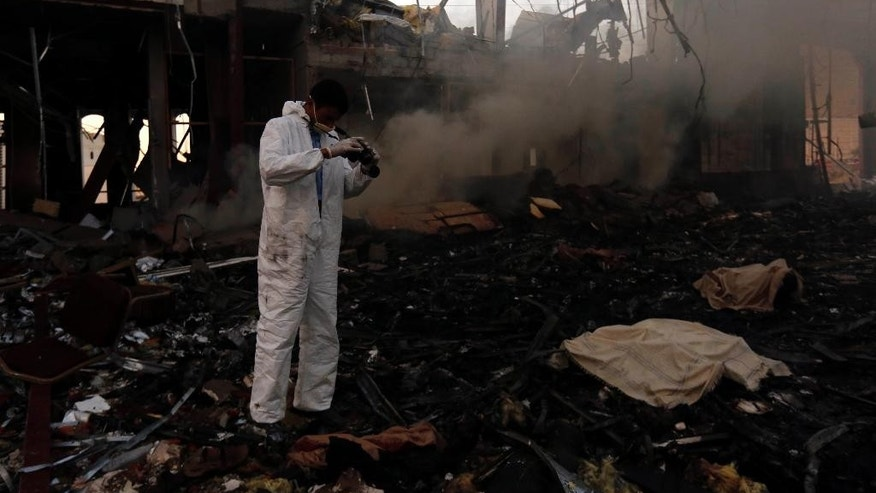 A man takes photos of the damage caused by a Saudi-led coalition airstrike in Sanaa, Yemen, Saturday, Oct. 8, 2016. Yemeni security and medical officials say at least 45 people have been killed in a Saudi-led coalition airstrike that targeted a funeral hall in the capital, Sanaa. The officials say at least another 100 have been wounded in the Saturday strike. (AP Photo/Osamah Abdulrhman)
