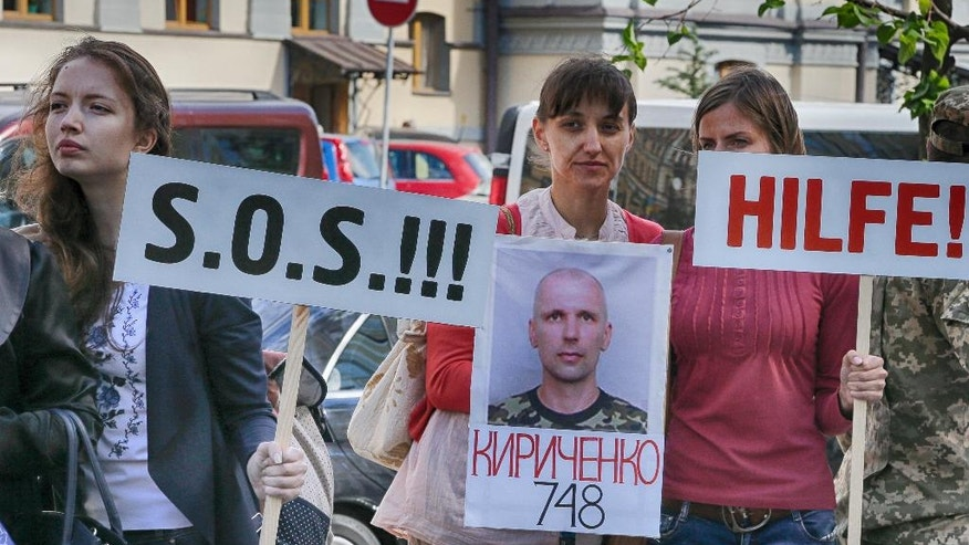 """FILE - In this photo taken Wednesday, Sept. 14, 2016, relatives of Ukrainian prisoners of war hold their portraits at a rally outside the German embassy in Kiev, Ukraine. Under the last Feb. Russia-Ukraine-France-Germany agreement on ending the war between Russia-backed separatists and Ukrainian forces, the sides agreed on an """"all-for-all"""" prisoner exchange. Although the numbers held by each side are in dispute, it's clear that the pace of release has slowed markedly for Ukrainians held by the rebels. Since the peace agreement was signed, 83 Ukrainian prisoners have been released, but only 12 of them were freed this year. (AP Photo/Efrem Lukatsky)"""