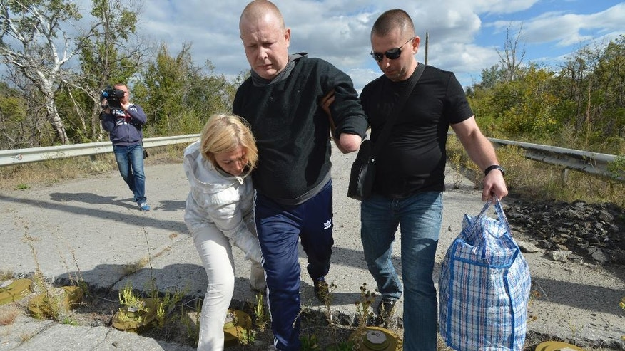 """FILE - In this photo taken Saturday, Sept. 17, 2016, Ukraine's deputy parliament speaker Irina Gerashchenko helps blind and armless volunteer Volodymyr Zhemchugov, center, to pass through a mine obstacle during an exchange of prisoners of war in the town of Shchastya in Ukraine's eastern Luhansk region.  Zhemchugov lost his arms and the use of his eyes in a 2015 mine blast in Ukraine's east during a war conflict with pro-Russian separatists. Under the last Feb.  agreement on ending the war between Russia-backed separatists and Ukrainian forces, the sides agreed on an """"all-for-all"""" prisoner exchange.  (AP Photo/Oleksandr Klymenko)"""