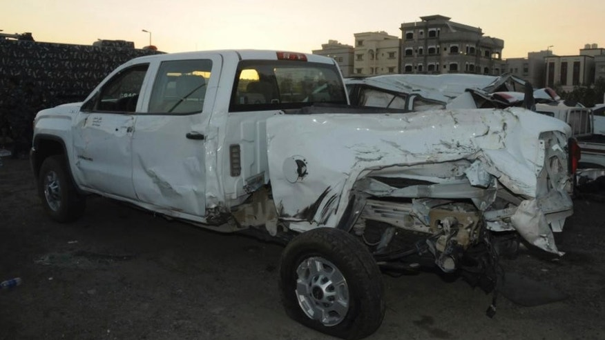 In this Saturday, Oct. 8, 2016 photo released by Kuwait Ministry of Interiors, a truck that carried five US soldiers is seen damaged after a garbage truck loaded with explosives and Islamic State papers rammed into it in Kuwait with only the Egyptian driver injured in the attack, authorities said. ( Kuwait Ministry of Interiors via AP)