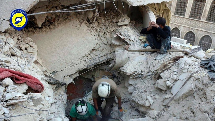 Oct. 4, 2016: Civil Defense workers from the White Helmets dig through rubble to remove bodies and look for survivors, after airstrikes hit the Bustan al-Basha neighborhood in Aleppo, Syria.