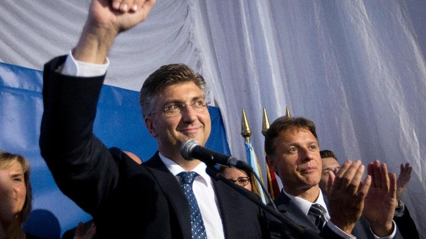 FILE - This is a  Monday, Sept. 12, 2016 file photo of Andrej Plenkovic, front left, leader of center-right HDZ party as he celebrates elections results at the party's headquarters in Zagreb, Croatia.  Croatia's president on Monday  Oct. 10, 2016 appointed conservative leader Andrej Plenkovic as prime minister-designate after his party and a small populist group agreed to form a coalition government in a bid to end months of political instability in the EU's newest member state. (AP Photo/Darko Bandic, File)