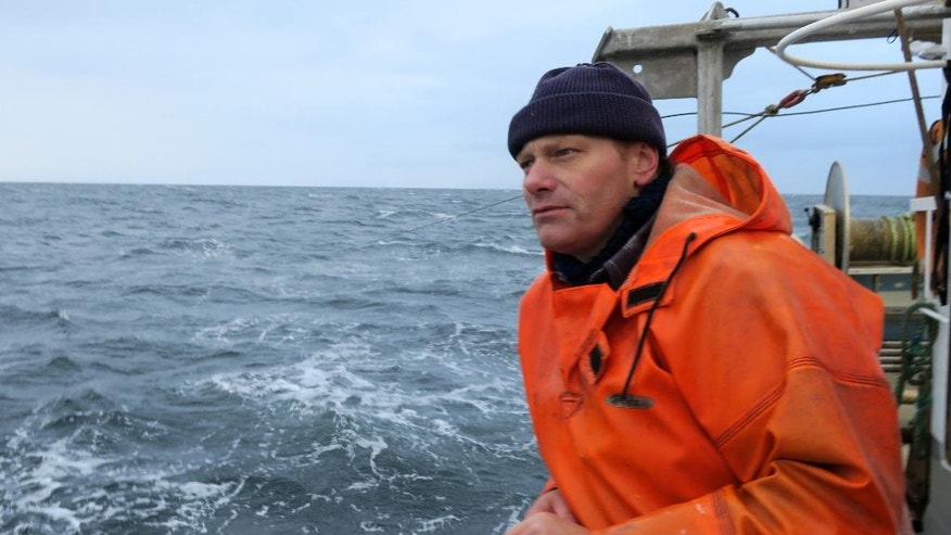 In this Thursday, Oct. 6, 2016 photo, Ulrik Koelle Hansen looks out from the fishing boat in the western part of the Baltic Sea. Ahead of next week's European Union meeting on whether to slash the fishing quota for dwindling cod stock in the western Baltic Sea, coastal fishermen fear they may have to go trawling elsewhere. (AP Photo/ Jan M. Olsen)