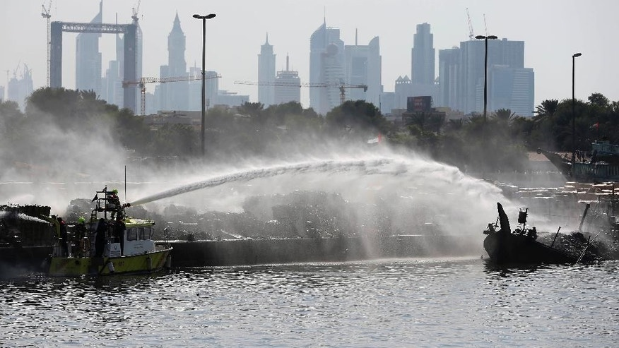 Smoke rises from a trading dhow as firefighters spray water to distinguish the fire at the Dubai creek in Dubai, United Arab Emirates, Monday, Oct. 10, 2016. (AP Photo/Kamran Jebreili)