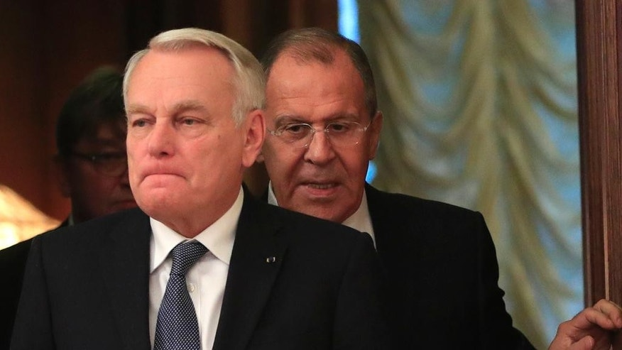FILE - In this Oct. 6, 2016 file photo, Russian Foreign Minister Sergey Lavrov, right, meets with French Foreign Minister Jean-Marc Ayrault in Moscow. Ayrault, speaking on Monday, Oct. 10, 2016, called on the International Criminal Court to investigate Russia for possible war crimes in Syria. (AP Photo/Pavel Golovkin, File)