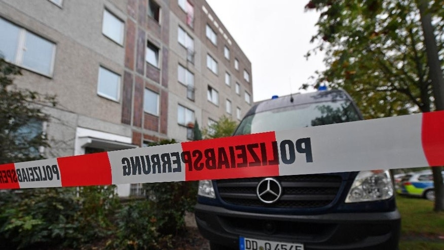 Oct. 10, 2016: A police barrier tape and a vehicle of a forensic team blocks off the entrance to an apartment in the Paunsdorf district of Leipzig, Germany.