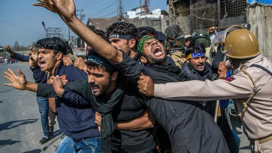 Kashmiri Shiite Muslims shout religious and pro-freedom slogan as Indian policemen stop them from for participating in a religious procession during curfew in Srinagar, Indian controlled Kashmir, Monday, Oct. 10, 2016. Authorities in Indian portion of Kashmiri imposed restrictions in some parts of Srinagar fearing religious processions marking the Muslim month of Muharram would turn into anti-India protests. (AP Photo/Dar Yasin)