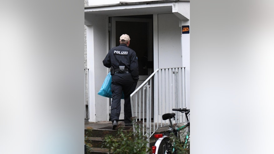 A police officer stands in front of the entrance to an apartment in the Paunsdorf district of Leipzig, Germany, Monday, Oct. 10, 2016. Two days after explosives were found in an apartment in Chemnitz, German police arrested a terror suspect, a Syrian national named Jaber al-Bakr, in Leipzig following a nationwide manhunt. (Hendrik Schmidt/dpa via AP)