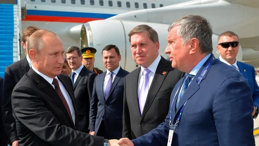 Russian President Vladimir Putin, left, shakes hands with CEO of state-controlled Russian oil company Rosneft Igor Sechin, right, as he arrives to attend a session of the World Energy Congress, in Istanbul, Monday, Oct. 10, 2016. Putin is set to meet Erdogan as the two push ahead with steps toward normalizing ties that were strained by Turkey's downing of a Russian warplane near the border with Syria last year. (Alexei Druzhinin, Sputnik,  Kremlin Pool Photo via AP)