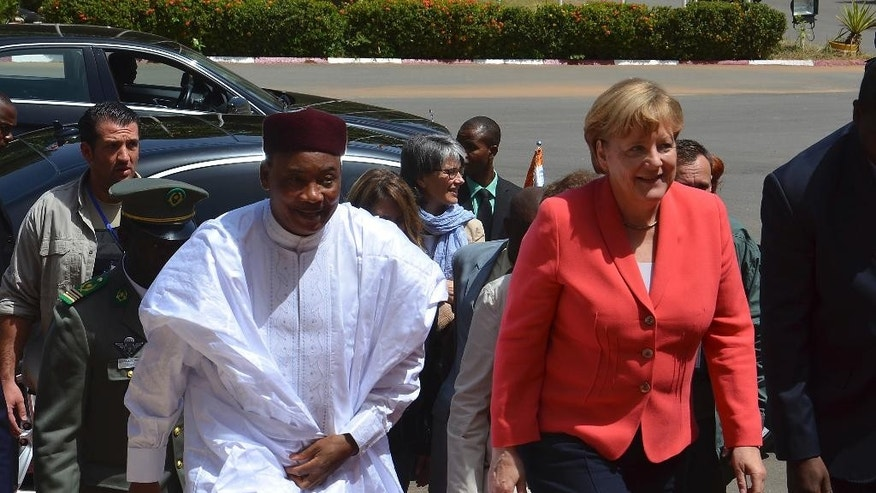 Niger President Mahamadou Issoufou, left, walks with  German Chancellor Angela Merkel before a meeting in Niamey, Niger, Monday Oct. 10, 2016. Niger's president said Monday that Germany can build a military logistics base in this West African country as it seeks to strengthen its support of the fight against extremism here and in Mali. President Mahamadou Issoufou spoke alongside German Chancellor Angela Merkel on the second leg of her three-nation African visit. (AP Photo/Moctar Ali Tondi)
