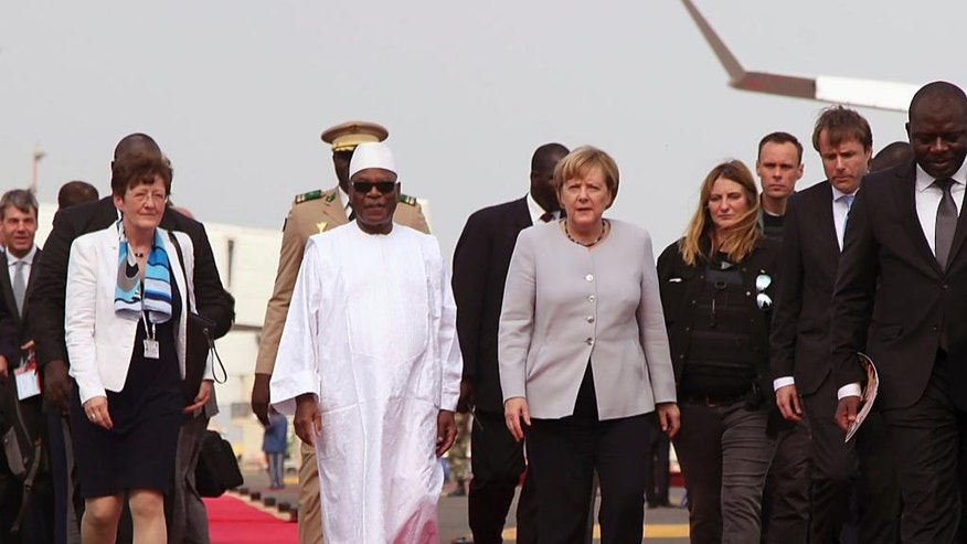 Malian President Ibrahim Boubacar Keita, center left, walk with German Chancellor Angela Merkel, center right, after her arrival at the airport in Bamako, Mali, Sunday, Oct. 9, 2016. German Chancellor  Merkel is on a three day tour in Africa, visiting, Mali, Niger, and Ethiopia. (AP Photo/Baba Ahmed)