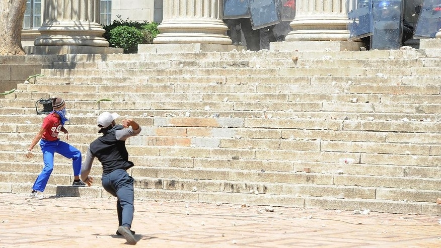 Students hurl stones on the University of the Witwatersrand campus in Johannesburg South Africa on Monday, Oct. 10, 2016. Tear gas and water cannon were fired as hundreds of students protested at the university amid a bitter national dispute with university managers and the government over demonstrators' demands for free education. (AP Photo)