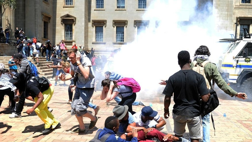 Students and police clash on the University of the Witwatersrand campus in Johannesburg South Africa on Monday, Oct. 10, 2016. Tear gas and water cannon were fired as hundreds of students protested at the university amid a bitter national dispute with university managers and the government over demonstrators' demands for free education. (AP Photo)