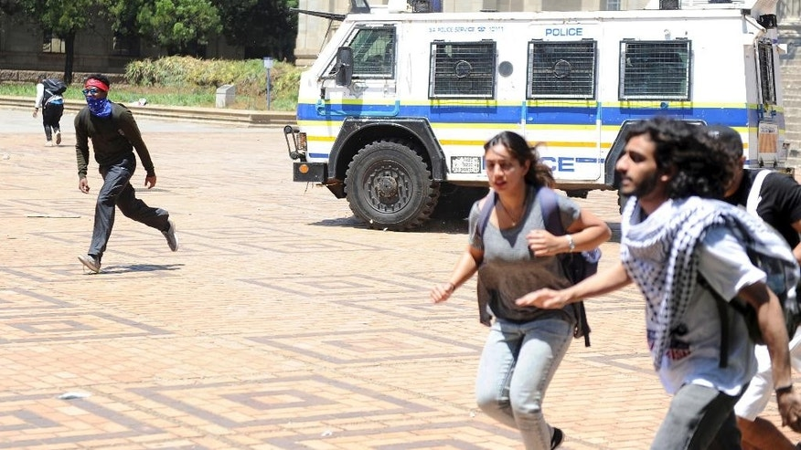 Students flee from a police vehicle on the University of the Witwatersrand campus in Johannesburg South Africa on Monday, Oct. 10, 2016. Tear gas and water cannon were fired as hundreds of students protested at the university amid a bitter national dispute with university managers and the government over demonstrators' demands for free education. (AP Photo)