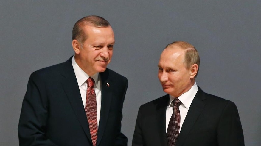 Turkey's President Recep Tayyip Erdogan, left and Russian President Vladimir Putin, right, shake hands Monday.