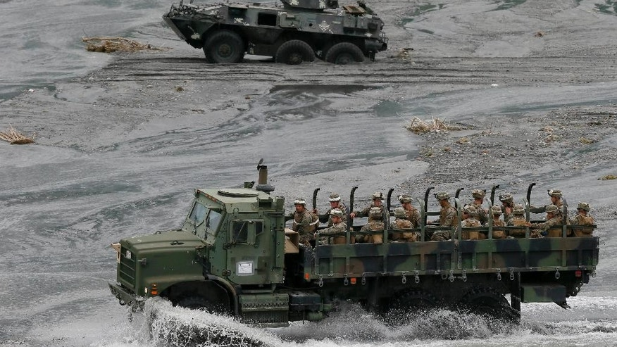 A military truck, foreground, carrying U.S. Marines from the 3rd Marine Expeditionary Brigade forces drives past a Philippine Marine APC (Armored Personnel Carrier) which got stuck in the sandy portion of a riverbed as they take part in a live-fire amphibious landing exercise dubbed PHIBLEX Monday, Oct. 10, 2016 in Crow Valley in Capas township, Tarlac province, north of Manila, Philippines. The combat drill, however, maybe the last under President Rodrigo Duterte, who has opposed the war games partly because they may upset China and because of his disgust over U.S. criticisms of his bloody anti-drug campaign. (AP Photo/Bullit Marquez)