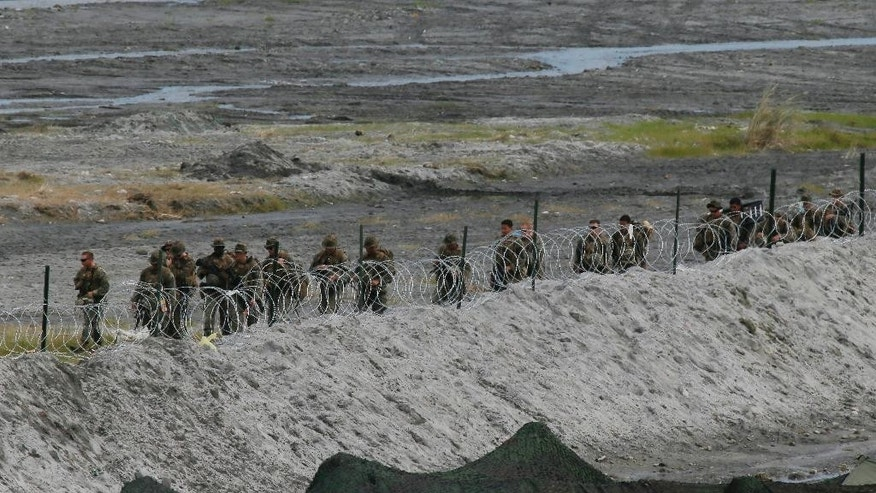U.S. Marines from the 3rd Marine Expeditionary Brigade walk in line as they prepare to take part in a live-fire amphibious landing exercise dubbed PHIBLEX Monday, Oct. 10, 2016 in Crow Valley in Capas township, Tarlac province, north of Manila, Philippines. The combat drill, however, maybe the last under President Rodrigo Duterte, who has opposed the war games partly because they may upset China and because of his disgust over U.S. criticisms of his bloody anti-drug campaign. (AP Photo/Bullit Marquez)