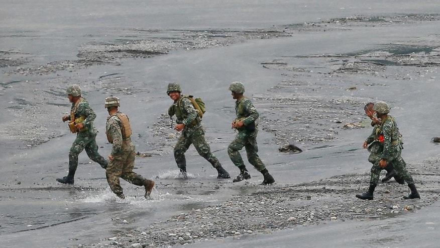 A U.S. marine, second from left, from the 3rd Marine Expeditionary Brigade, runs to their vehicle with his Philippine counterparts as they take part in a live-fire amphibious landing exercise dubbed PHIBLEX Monday, Oct. 10, 2016 in Crow Valley in Capas township, Tarlac province, north of Manila, Philippines. The combat drill, however, maybe the last under President Rodrigo Duterte, who has opposed the war games partly because they may upset China and because of his disgust over U.S. criticisms of his bloody anti-drug campaign. (AP Photo/Bullit Marquez)