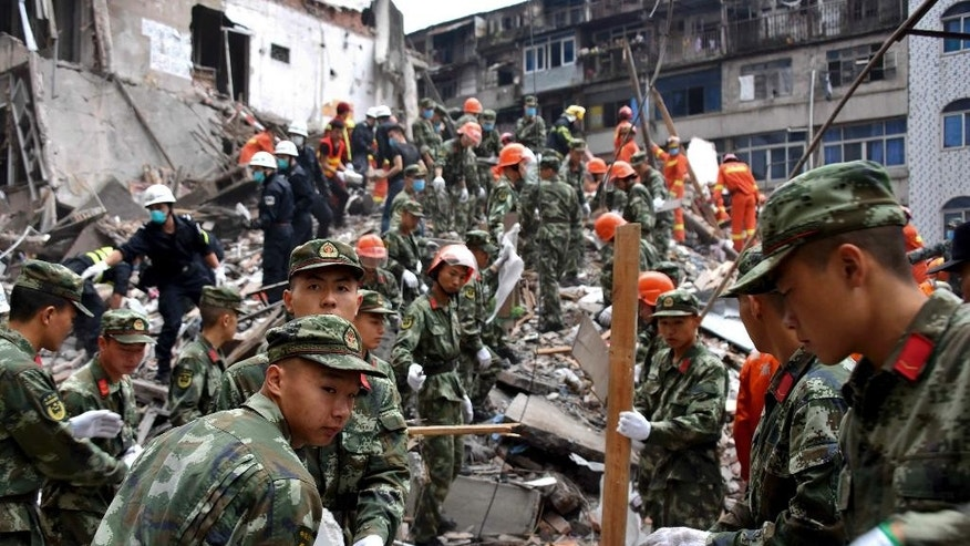 Rescuers clear the debris to search for victims on the site of collapsed residential buildings in Wenzhou city in east China's Zhejiang province, Monday, Oct. 10, 2016. More than dozen people were believed to be buried after four residential houses collapsed on Monday early morning. (AP Photo)