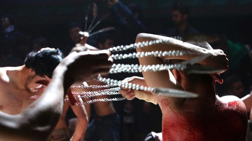 In this Sunday, Oct. 9, 2016 photo, Shiite Muslim men beat themselves with knives attached to chains during a procession to mark Ashoura in Kabul, Afghanistan. Afghanistan's Shiite population is marking the death of Hussein, the grandson of the Prophet Muhammad, at the Battle of Karbala in present-day Iraq in the 7th century.(AP Photo/Rahmat Gul)