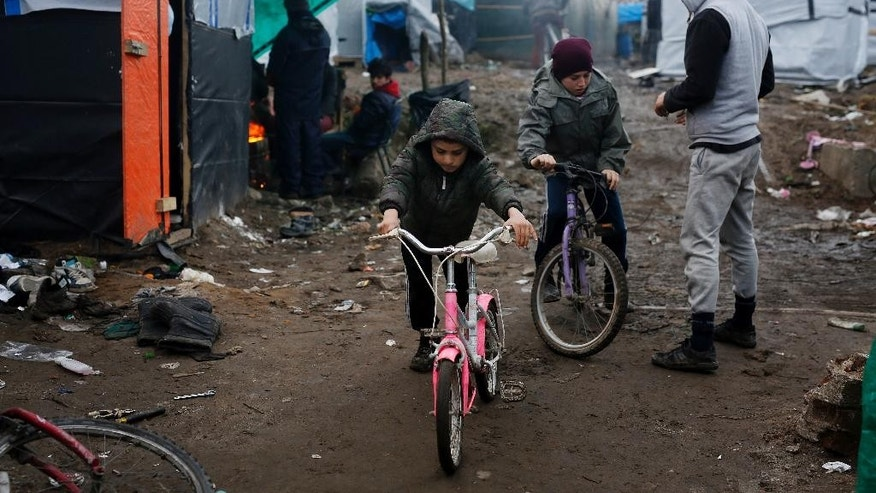 FILE - In this Feb. 25, 2016 file photo, Afghan children ride their bicycles in a makeshift migrants camp near Calais, France. The U.K. government said on Monday, Oct. 10, 2016 that within days, Britain will begin admitting hundreds of children from a border refugee camp on the French side of the English Channel. (AP Photo/Jerome Delay, File)