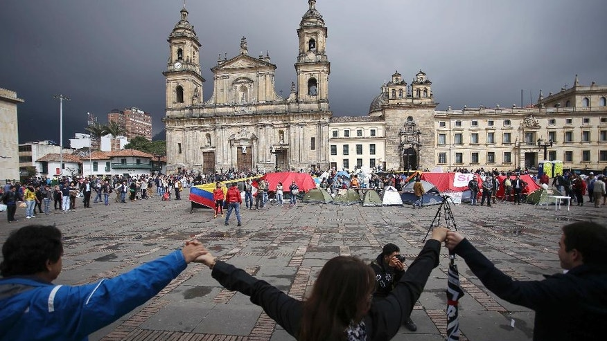 Demonstrators hold hands to support a peace accord between the Colombian government and rebels of the Revolutionary Armed Forces of Colombia, FARC, at the main square in Bogota, Colombia, Saturday, Oct. 8, 2016. Dozens of people are camping at the Bolivar square in support of the peace process. Voters narrowly rejected in a referendum a peace accord signed between President Juan Manuel Santos and the FARC. (AP Photo/Ivan Valencia)