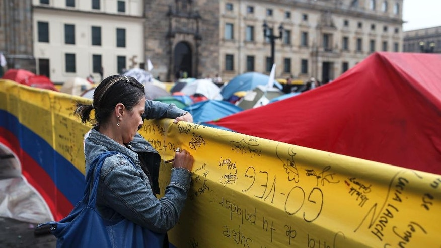 A woman writes a message to support a peace deal between the Colombian government and rebels of the Revolutionary Armed Forces of Colombia, FARC, at the main square in Bogota, Colombia, Saturday, Oct. 8, 2016. Dozens of people are camping at the Bolivar square to support the continuation of peace talks.   Dozens of people are camping at the Bolivar square to support the continuation of peace talks. Voters narrowly rejected in a referendum a peace accord signed between President Juan Manuel Santos and the FARC. (AP Photo/Ivan Valencia)