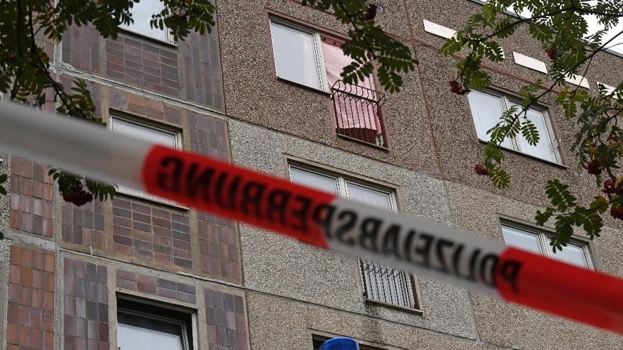 A pink curtain covers an opened window of an apartment in the Paunsdorf district of Leipzig, Germany, Monday, Oct. 10, 2016. Two days after explosives were found in an apartment in Chemnitz, German police arrested a terror suspect, a Syrian national named Jaber al-Bakr, in Leipzig following a nationwide manhunt. (Hendrik Schmidt/dpa via AP)