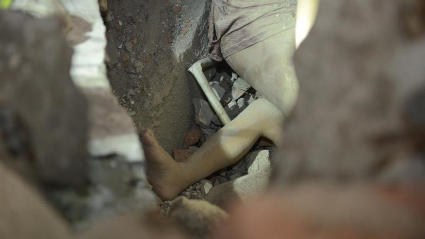 One leg of a young girl who survived the collapse of buildings is seen in the rubble.