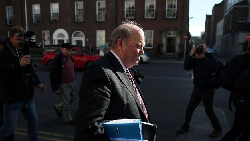 Finance Minister Michael Noonan, centre, makes his way to Government buildings to deliver the Irish Budget, in Dublin, Tuesday Oct. 11, 2016. Ireland has unveiled a 2017 budget that builds on the country's rapid recovery from an international bailout with 1.3 billion euros ($1.45 billion) of spending increases and tax cuts. Finance Minister Michael Noonan says he expects Ireland's economy to grow 4.2 percent this year but only 3.5 percent next year because of the negative impact of the United Kingdom's planned exit from the European Union. ( Brian Lawless/PA via AP)