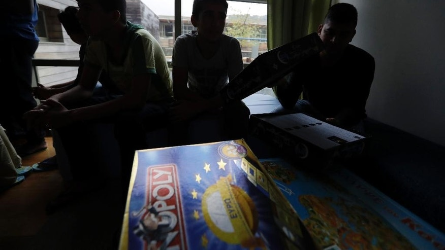 Migrant children play board games at a new reception center for unaccompanied minors in Athens, Tuesday, Oct. 11, 2016. The Balkan route, used by nearly 1 million migrants last year to cross to mainland Europe, was closed last March and over 60,000 people are stranded in Greece. (AP Photo/Thanassis Stavrakis)